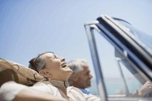 older couple in car enjoying retirement